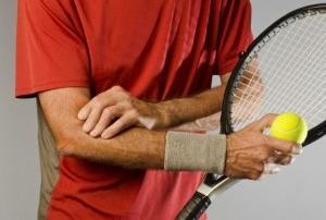 A tennis player holding elbow in pain