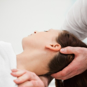 osteopath manipulating the neck of a woman
