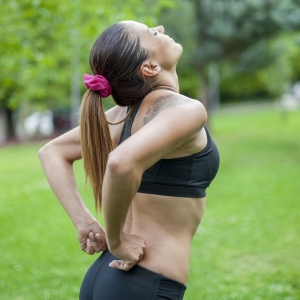 Woman suffers from back pain during sports activity