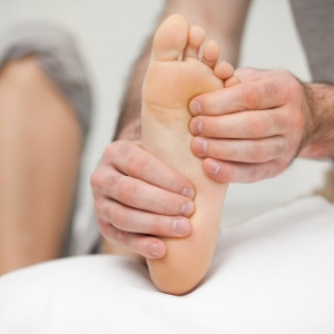 Osteopath palpating the sole of the foot of a patient in his office